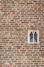 Brugge, Flanders, Belgium - August 4, 2021: Smallest Spy Window With Stained Glass In Brown Brick Wall Of Gruuthuse Palace.