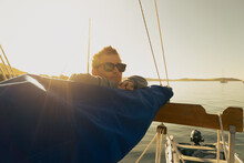 Young Man Leaning On The Boom Of A Traditional Gaff Rig Sailing Boat At Sunrise In Falmouth Harbour