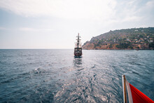 Old Pirate Ship On The Water Of Mediteranean Sea. Tourist Entertainment, Coastal Tour. Summer Sunny Day. Mountain Shore Of Alanya. Turkey.