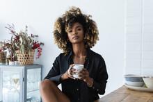 Charming Black Woman Drinking Beverage In Kitchen