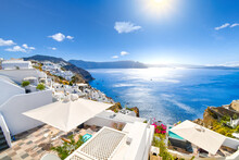 The Whitewashed Hillside Town Of Oia, Greece, Filled With Cafes And Hotels Overlooking The Aegean Sea And Caldera.