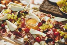 Charcuterie Board With Maasdam, Camembert, Brie, Cheddar Cheese And Prosciutto, Salami, Figs, Honey,grapes And Cherry Tomatoes. Antipasti On Wood, Mediterranean Appetizers On A Sunny Picnic