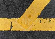 Shoe Or Trainer Footprint In Paint.  Yellow Painted Line With Foot Print Left Behind Stood On Whilst Wet.  Black Tarmac And Bright Yellow Lined Paint.