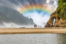 Family Adults And Children Walking On The Ocean Beach With Incredible Sunlit Rainbow Sky And Sun Rays In The Early Morning Mist.