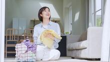 リビングで洗濯物を畳む若い女性
