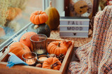 Fototapeta Kawa jest smaczna - Autumn cozy mood composition on the windowsill. Pumpkins, cones, candles on wooden tray, blurred Fall mood message on lightbox, warm plaid. Autumn, fall, hygge home decor. Selective focus. Copy space.