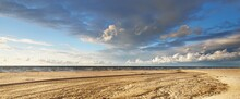 Epic Cumulus Clouds Above The Sandy Baltic Sea Shore After A Thunderstorm. Dry River, Sand Texture Close-up. Latvia. Dramatic Sky. Ecology, Environmental Conservation, Fickle Weather, Climate Change