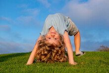 Happy Kid Boy Girl Standing Upside Down On Her Head On Grass In Summer Day. Funny Cute Child Doing Fun Exercise.