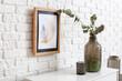 Leinwandbild Motiv Vase with candle on shelf near brick wall