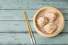 Bamboo Steamer With Tasty Dumplings And Chopsticks On Color Wooden Background