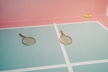 Pair Of Tennis Rackets And Balls On Court
