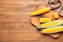 Board With Fresh Corn Cobs On Wooden Background