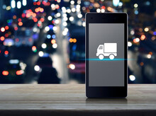 Truck Delivery Flat Icon On Modern Smart Mobile Phone Screen On Wooden Table Over Blur Colorful Night Light City With Road And Cars, Business Transportation Online Concept
