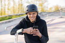 A Teenager Waits For Classmates At The Skatepark With His Bike After School. Boy Sits With Helmet And Phone In Hand Waiting For A Call From Friends