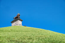 Lion Of Waterloo Or Lion's Mound In Belgium On The Green Hill Against A Clear Blue Sky