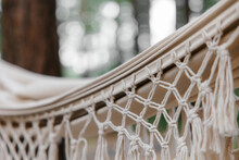 A Linen Hammock With A Fringe Hangs On A Stand. Summer, Pine Forest. The Concept Of A Picnic And Outdoor Recreation.