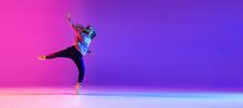 Attractive Young Girl Dancing Hip-hop Isolated On Gradient Pink Purple Neon Studio Background