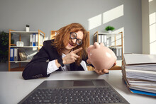 Strange Crazy Guy Freak With Round Glasses Talks To A Piggy Bank Sitting At A Table In Front Of A Laptop In The Office. Concept Of Humorous Caricature On Saving Money And Earnings.