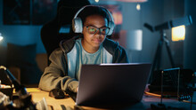 Young Teenage Multiethnic Girl Using Laptop Computer And Wearing Headphones In A Dark Cozy Room At Home. She's Browsing Educational Research Online. Studying Science School Homework Concept.