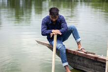 A Young Boy Is Sitting On A Piece Of Wood Leans On The Stick, Wearing A Dark Blue Shirt And Is Upset, And His Behind A River Green Nature Background Blur.