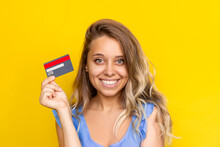 Close-up Of A Young Charming Smiling Blonde Woman With Wavy Hair Holding A Plastic Credit Card In Her Hand Isolated On A Color Yellow Background. Shopping, Payment For Purchases, Banking Operations