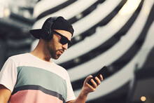 Young Man With Black Hat And Headphones Holding Smartphone In Hand And Listening To Music In The City