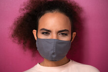 Questioning Or Studying Look Wearing Reusable Face Mask African American Charming Girl In Peachy T-shirt, To Prevent Others From Corona COVID-19 And SARS Cov 2 Infection Isolated On Pink Background.