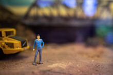 Toy Model Of Male Foreman Worker Standing In Front Of Truck In The Construction Site.