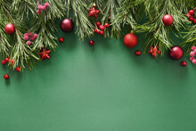 Christmas Winter Frame With Evergreen Pine Branches, Red Balls On Green Background. Xmas Greeting Card. Holiday Time. Happy New Year. Space For Text. View From Above, Flat Lay.