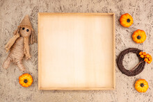 Wooden Frame Template With Copyspace And Fall Decor From Pumpkins And Straw Doll On Golden Background.