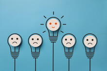 A Lot Of Sad Non-burning Light Bulbs And One Joyful Burning Light Bulb. A Symbol Of The Creative Idea That Has Arisen And A Positive