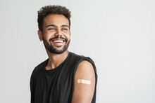 Man Smiling After Receiving Vaccination, Young Men Received A Corona Vaccine Looking Away Isolated On Gray Background.