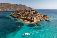 Panoramic View Of Spinalonga Island With Ships And Turquoise Sea Filmed From A Drone