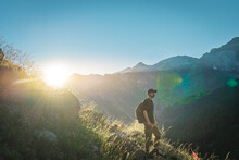 Young Man Trekking On The Top Of A Green Mountain Enjoying The Amazing Landscape Views During Sunset. Paradise Grass Mountain. Lifestyle Relax And Freedom. The Beauty Of Nature Concept.