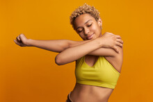 Studio Shot Of Stretching African Girl With Curls And Piercing, Wearing Yellow Sport Top, Holding Her Hand With Small Scar Around Shoulder, Eyes Closed In Pleasure. People And Body Positive Concept
