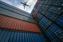 Freight Airplane Flying Above Overseas Shipping Container . Logistics Supply Chain Management And International Goods Export Concept .