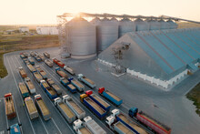 Grain Terminals Of Modern Sea Commercial Port. Silos For Storing Grain In Rays Of Setting Sun. Many Trucks Are Waiting In Line For Unloading In Port Harbor, Top View From Quadcopter. Logistics, Trade
