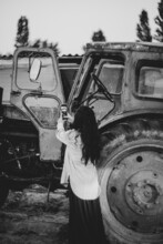 Black White Photo As A Girl Takes Pictures Of An Old Tractor