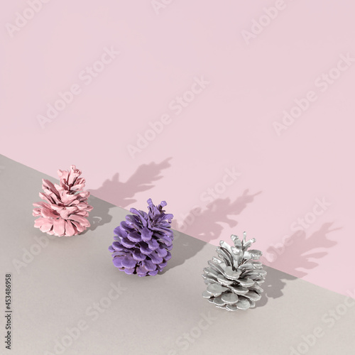 Creative composition made with three painted pinecones with sunshine shadows against pastel pink and gray background. Minimal nature concept with copy space. Art direction.