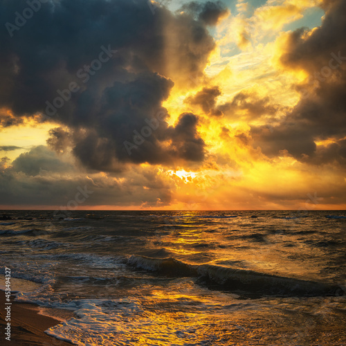 Beautiful rays of the sun through textured clouds. Sea beach and incoming sea waves against the backdrop of a delightful sunrise or sunset.
