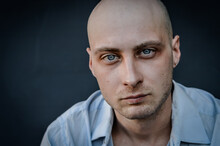 Portrait Of A Young Bald Man With A Grumpy Look Staring In Front Of Him