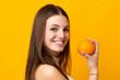 Leinwandbild Motiv Young caucasian woman holding an orange isolated on orange background