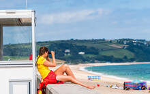 Female Lifeguard At The Station Over Beach And Sea, Torcross, Devon, England, Europe