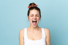 Young Caucasian Woman Isolated On Blue Background Shouting To The Front With Mouth Wide Open