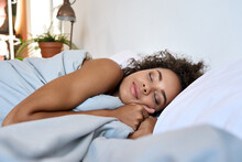 Serene Peaceful Millennial African American Mixed Race Woman Laying Sleeping Having Rest On Soft Pillow In Modern Bedroom With Eyes Closed And Pleasure On Her Face In Sunlight Morning. Close Up.
