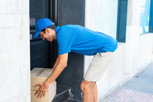 Young Delivery Man At Outdoors Leaving The Boxes At The Door