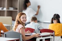 Joyful Redhead Schoolgirl Smiling At Camera While Blurred African American Teacher Writing On Whiteboard