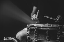 Drummer Playing Drum Sticks On A Snare Drum On Black Background Copy Space.