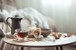 Leinwandbild Motiv A cup of tea and a teapot on a blurred background of the interior of the room.
