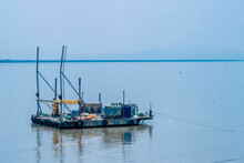 Small Barge With Yellow Crane Moored In Harbor With Hazy Sky In Background.